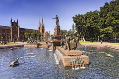 Sy HP Fount Right Side Day. Bright sunny day in Sydney's Hyde park. Fresh water fountain pool surrounded by tall green trees and St Mary's cathedral in municipal Royalty Free Stock Image