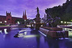 Sy Hyde P Fount 17 Set. AUstralia sydney central Hyde Park Archibald fountain at sunset with St Mary Cathedral blurred water illuminated landmark Royalty Free Stock Photo