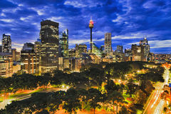 Sy hyde park dark 2 city. Inside sunset over Sydney city downtown from Hyde park towards high-rises and towers. Brightly illuminated city architecture between Stock Photo