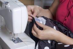Sy kläder av en individuell entreprenör En kvinna arbetar på en symaskin Staples snittbeståndsdelarna av produkten Royaltyfri Fotografi