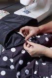 Sy kläder av en individuell entreprenör En kvinna arbetar på en symaskin Staples snittbeståndsdelarna av produkten Royaltyfri Foto