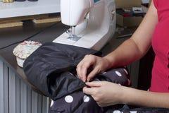Sy kläder av en individuell entreprenör En kvinna arbetar på en symaskin Staples snittbeståndsdelarna av produkten Royaltyfria Foton
