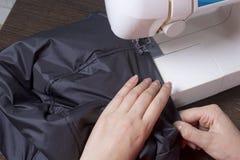 Sy kläder av en individuell entreprenör En kvinna arbetar på en symaskin Staples snittbeståndsdelarna av produkten Arkivbilder