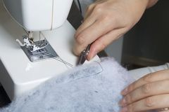 Sy kläder av en individuell entreprenör En kvinna arbetar på en symaskin Staples snittbeståndsdelarna av produkten Royaltyfri Bild