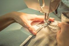Sy kläder på en symaskin arkivbild
