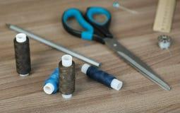 Sy levererar sax, tråden, spolar, blyertspennan, en linjal på trätabellen royaltyfria foton