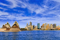 Sy Mid Harb Circ Quay Dist. Panorama of Sydney city CBD behind Circular quay across Harbour with tall towers of business and office high-rises on a sunny bright Stock Images