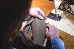 Sy processen av läderbältet gamal mans händer bak att sy Läderseminarium sy för textiltappning som är industriellt royaltyfri foto