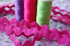 Sy Tid! Ordna till med tre färgrika rullar av tråd i purpurfärgat, rosa och grönt royaltyfri foto