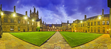 Sy Uni Courtyard pan. Australian tertiary education institution - university in Sydney at sunset. Panoramic courtyard of main historic building on university Stock Photos