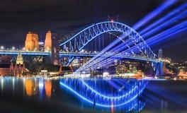 Sy vivid 17 Bridge Beams Reflect. Sydney harbour bridge illuminated during vivid sydney light festival. Bright blue light beams project from Overseas passenger Stock Photography