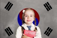 Sydkorea begrepp med ungeliten flickastudenten med den röda boken mot den Sydkorea flaggabakgrunden royaltyfri fotografi