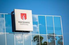 Macquarie University logo on glass window building.