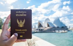 A man`s hand holding Thailand passport with blurred background of Sydney Opera House for Concepts of traveling. SYDNEY, AUSTRALIA. – On December 14, 2017 stock image