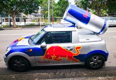 Red Bull energy drink mini cooper publicity car with a can of red bull drink behind. Used for promotion. stock photography