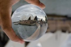 Opera house with cloudy sky photography in clear crystal glass ball with left hand male holding. SYDNEY, AUSTRALIA – On January 11, 2018. – Opera house with Royalty Free Stock Image