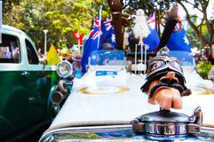 A man face cartoon toy model attached on the hood of the Vintage car and decorate with Australia flag in the Classic motor show. SYDNEY, AUSTRALIA. - On January royalty free stock photo