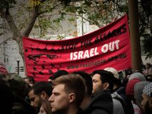 The Palestinians protest against Israel to free Palestine, They show image says ` Stop the attacks Israel out ` at Sydney Townhall. Sydney, Australia. - On July stock photo