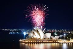 Series of pink fireworks creating a beautiful display over the Sydney Opera House and harbor. Sydney, Australia - March 8, 2018 - A huge burst of pink fireworks stock photo