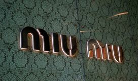Ð¡lose-up shot of Miu Miu store logo sign. Miu Miu is an Italian high fashion women`s clothing and accessory brand stock photography