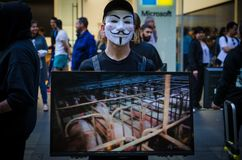 Groups of people put on the anonymous mask and hold the screen monitor to share information about cruelty of animal agriculture. SYDNEY, AUSTRALIA. - On October stock images