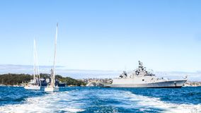 Two sailboats sail pass INS Sahyadri F49 Indian Navy Frigate in Sydney harbor during International Fleet Review Sydney 2013 stock images