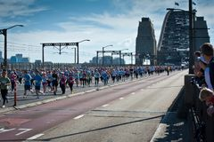 Crowds running on the road across the Sydney Harbour Bridge for a fun run royalty free stock photography