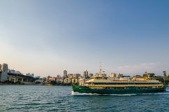 Sydney harbour with the ferry in sunset lights and cityscape view behind. royalty free stock images