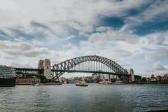 SYDNEY, AUSTRALIEN - 26. FEBRUAR 2017: Die Hafen-Brücke, mit dem Sydney im Hintergrund Lizenzfreie Stockfotos