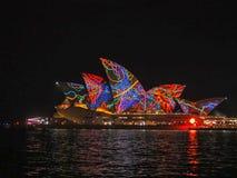 SYDNEY AUSTRALIEN - JUNI 3 2015: psykedelisk sydney operahus som tänds ljust med multicolours och modeller royaltyfri foto