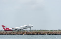 SYDNEY, AUSTRALIEN - 11. NOVEMBER 2014: Internationaler Flughafen Sydnay mit entfernen Flugzeug Flugzeuge VH-OJS, Boeing 747-438, Lizenzfreie Stockfotos