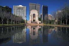 SYDNEY AUSTRALIEN - Sept 12 2015 - Anzac Memorial framme av en manmade sjö med byggnader som bakgrund på Hyde Park Sydney Royaltyfria Foton