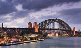 Sydney Bridge Terminal Quay. Harbour bridge in Sydney - side view from Circular Quay at sunset under heavy clouds highly illuminated Royalty Free Stock Photo