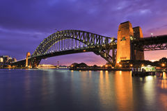 Sydney Bridge Whole Arch Milsons. Side view of a whole still arch of famous Sydney Harbour bridge at sunset against setting sun behind clouds Stock Photo