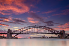 Sydney city harbour and bridge cityscape panoramic. View at sunrise with warm sun light blue and pink sky Stock Images