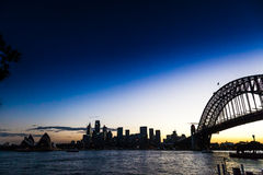 Sydney City. A view of Sydney at night from the north shore at Kirribilli. The sun is setting behind the harbour bridge and the city lights have come on royalty free stock photography