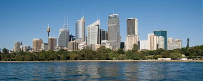 Sydney Commercial Skyline4. Sydney skyline, blue sky and Sydney Harbor water reflections. NSW.Australia Stock Photo