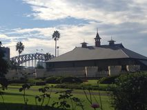 Sydney Conservatorium of Music gardens. Sydney Botanical Gardens buildings bridge palms castle turrets grass skyline clouds Sydney Royalty Free Stock Photography