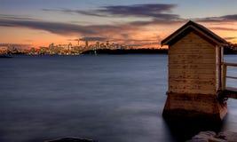 Sydney at dusk. A small hut on a bay overlooks Sydney city at sunset Royalty Free Stock Photos