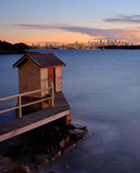 Sydney at dusk. A small hut on a bay overlooks Sydney city at sunset Royalty Free Stock Photography