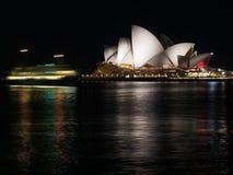 Sydney hamn med ljusa strimmor för färja och operahus vid natt Royaltyfria Foton