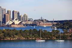 Sydney harbour environment with Opera House. Overlooking Sydneys harbour area: with the Opera House, The Rocks district, an airplane flying over the city and Royalty Free Stock Photo