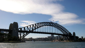 Sydney Harbour Bridge. From the water with a puffy white cloud Stock Photos