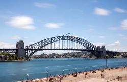 Sydney Harbour Bridge avec de l'eau les nuages troubles et Photos stock