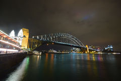 Sydney Harbour Bridge, Central Business District & brightly lit Luna Park on the left at night. This image is taken along Luna Park sidewalk with Dawes Point Stock Photo