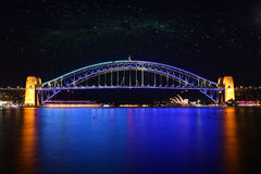 Sydney Harbour Bridge at Night, Australia. SYDNEY, AUSTRALIA - JUNE 2, 2014; The Sydney Harbour Bridge glows in a colours of beautiful blue and aqua during Vivid Royalty Free Stock Image