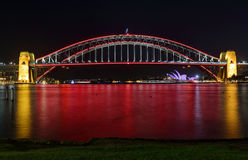 Sydney Harbour Bridge in Red. SYDNEY, AUSTRALIA, MAY 23, 2015;  Sydney Harbour Bridge in the colour of red and reflections turn the harbour vivid red too Stock Photos