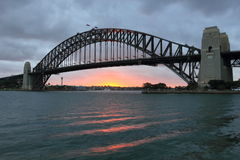 Sydney Harbour Bridge at sunset by clouded sky Royalty Free Stock Photos