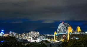 Sydney Harbour Bridge and surrounding cityscape illuminated at night in Australia. As seen from the hill at the observatory Stock Photos