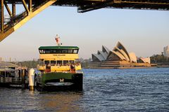 The Sydney Opera House and a Harbour Ferry at Sunset, Australia. A Sydney Harbour ferry boat docked at Milsons Point on the Harbour North Shore, with a view royalty free stock images